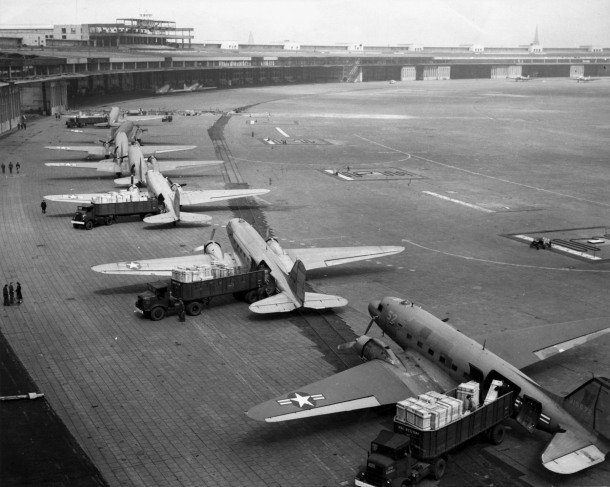 U.S. Navy Douglas R4D and U.S. Air Force C-47 aircraft unload at Tempelhof Airport during the Berlin Airlift.